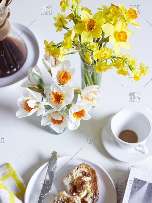 Bouquets of daffodils on a table with coffee and toast