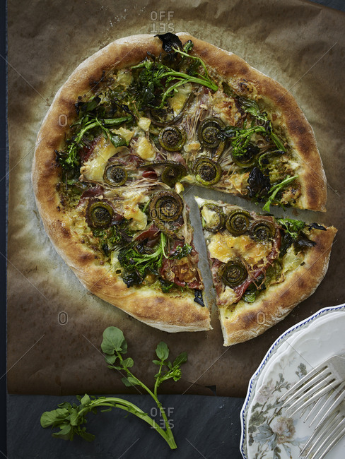 Fiddlehead fern pizza on wooden cutting board
