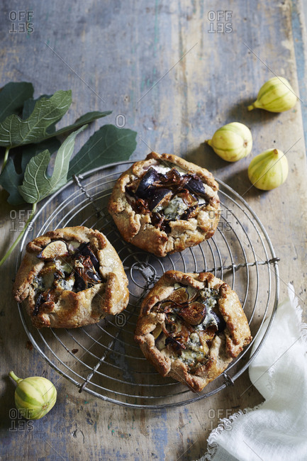 Three fig tarts on cooling rack with whole figs