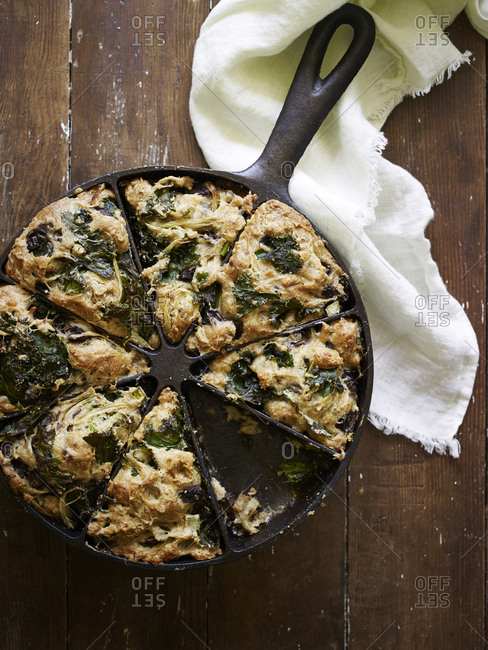 Cast iron pan with kale and mushroom scones with slice removed