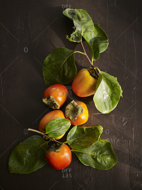Fresh-picked persimmon fruit on wooden surface
