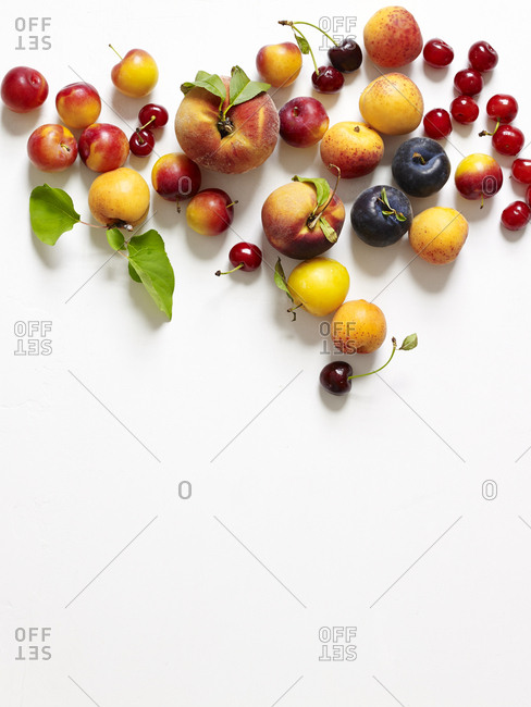 Overhead view summer stone fruits on white background