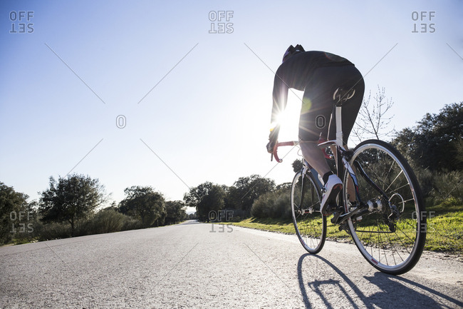 Man riding a bicycle on a country road in Madrid, Spain