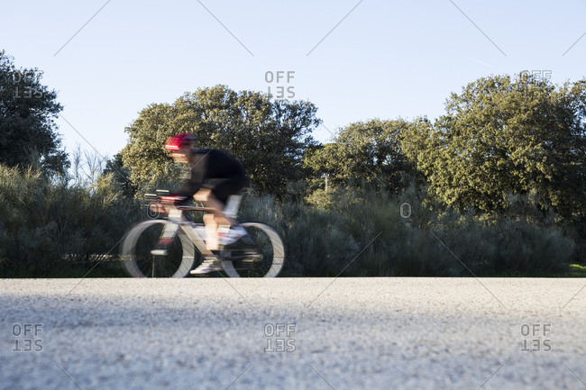 Unfocused man riding a bicycle on a road in Madrid, Spain