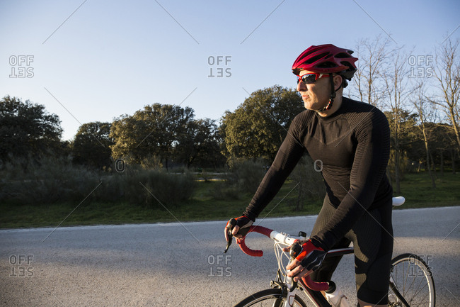 Man with sunglasses, bike helmet, and bicycle at sunset in Madrid, Spain