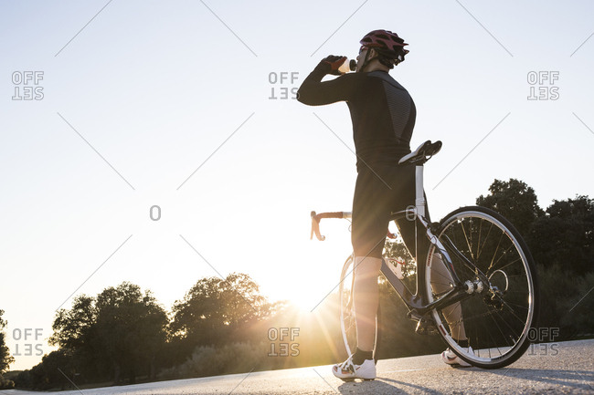 Cyclist drinking during a bicycle training in a road at sunset in Madrid, Spain