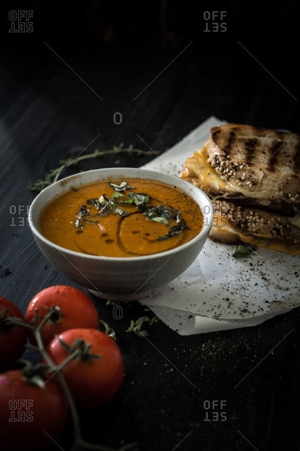Grilled cheese by bowl of tomato soup