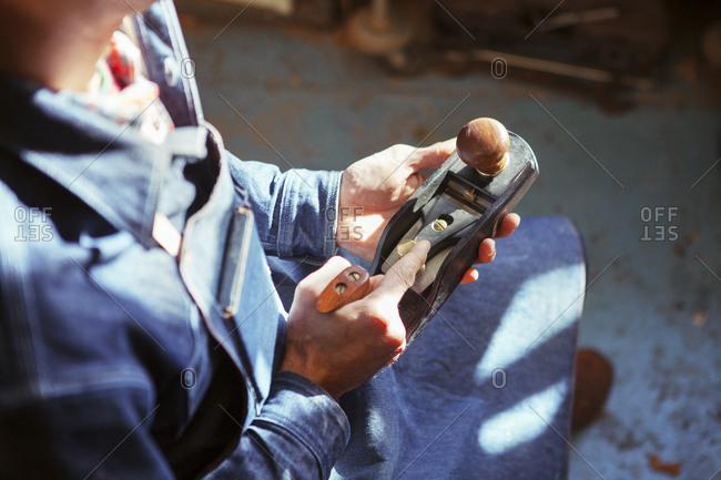 Midsection of carpenter holding wood plane at workshop
