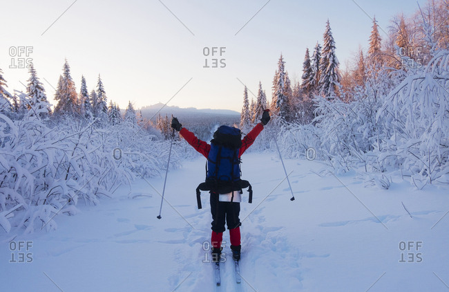 Rear view of hiker with arms raised standing on snow covered field against clear sky