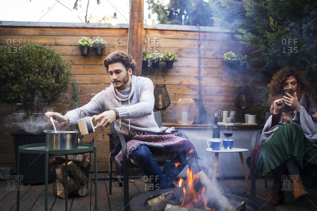 Man taking food while female friend using mobile phone by fire pit in backyard