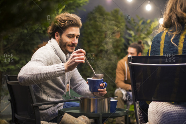 Man pouring drink in cup while sitting with friends at backyard