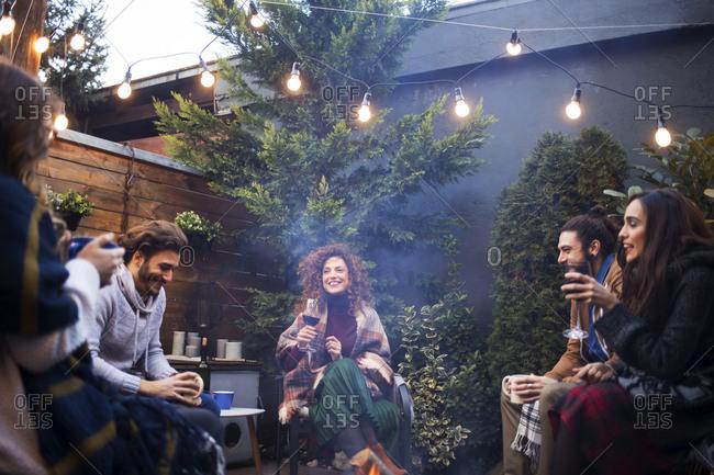 Cheerful friends talking while enjoying drinks in backyard