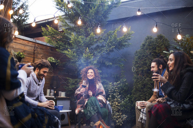 Cheerful friends talking while enjoying drinks in backyard