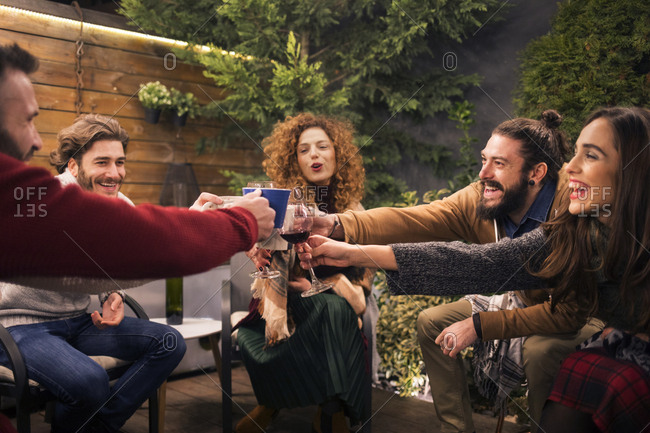 Cheerful friends toasting drinks in party at backyard