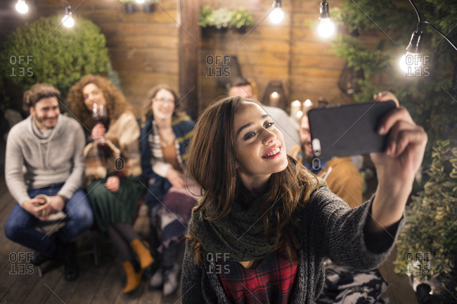 Woman taking selfie with friends in backyard at night