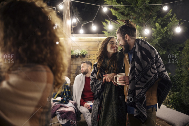 Romantic couple enjoying party with friends in backyard at night