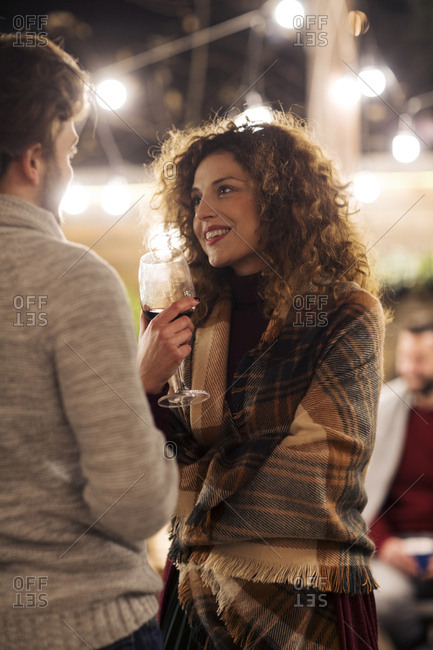 Woman with wine talking to male friend in backyard at night
