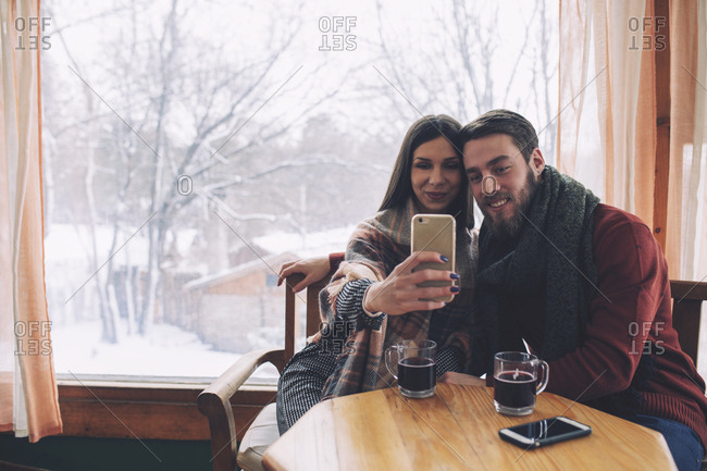 Woman with boyfriend taking selfie while sitting by window in cafe