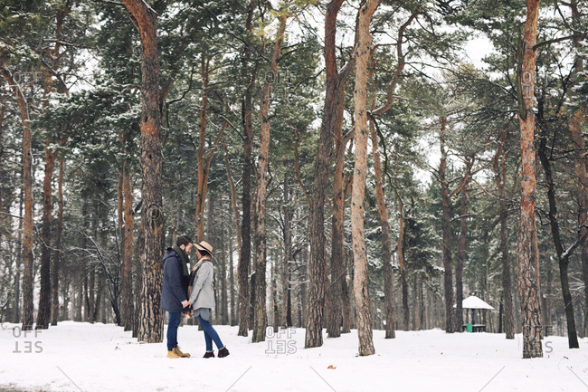Happy couple looking at each other while standing on snowy field in forest