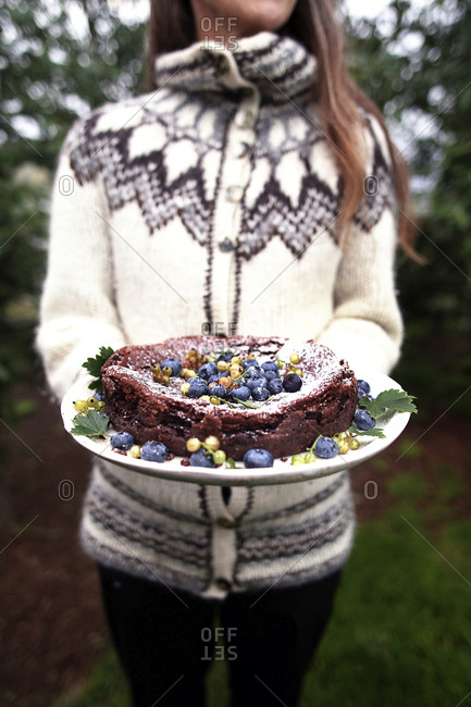 Midsection of woman holding cake while standing on field in yard