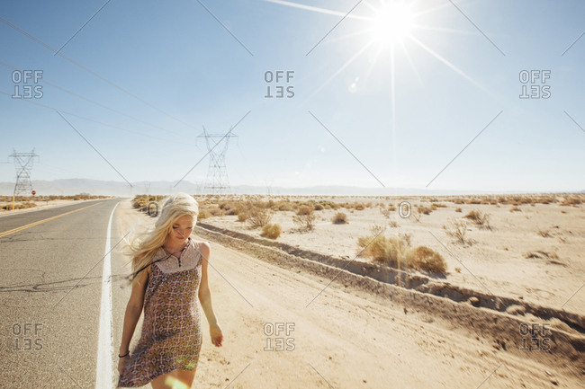 Woman walking on road by desert during sunny day