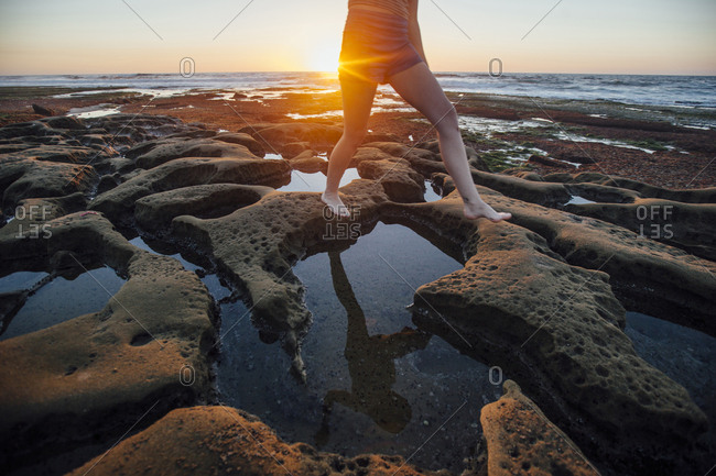 Low section of woman walking at rocky beach during sunset