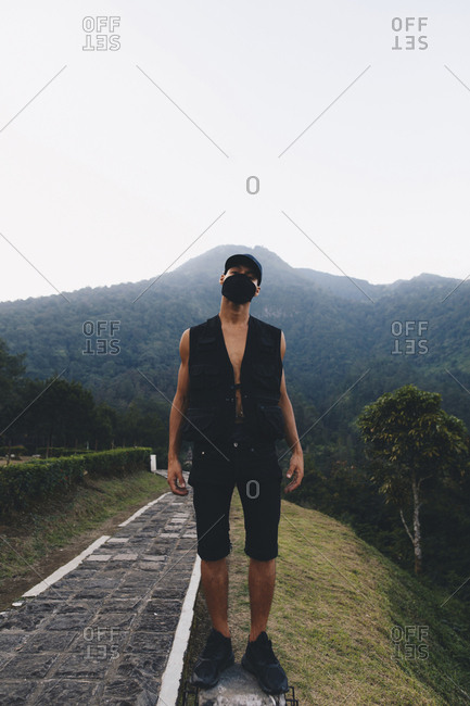 Portrait of man wearing mask while standing on mountain against clear sky