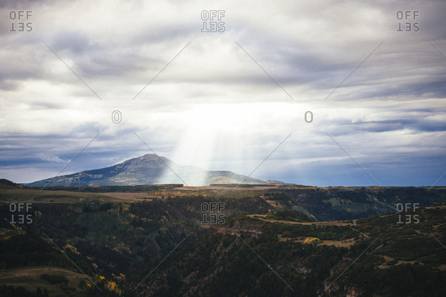 Sunlight falling on landscape against cloudy sky