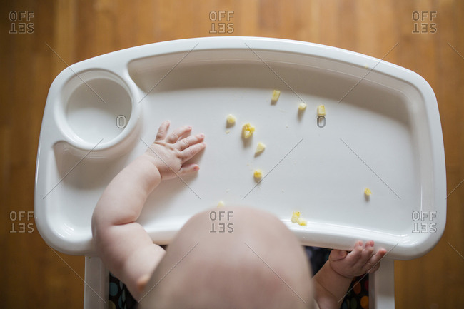High angle view of baby girl playing with banana while sitting on high chair at home