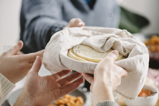 Cropped image of friends passing tortilla while having food at table