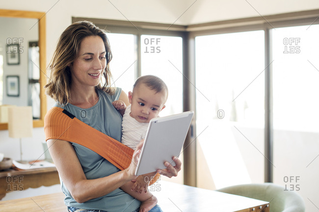 Mother carrying baby boy in carrier while using tablet computer at home