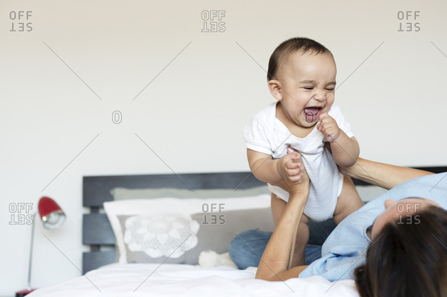 Cheerful baby boy playing with mother on bed at home