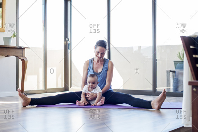 Mother holding baby boy while exercising at home