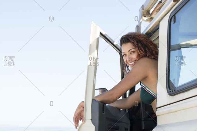 Portrait of happy woman sitting on off-road vehicle against clear sky at beach