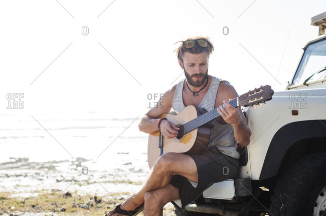 Man playing guitar while sitting on off-road vehicle during sunny day