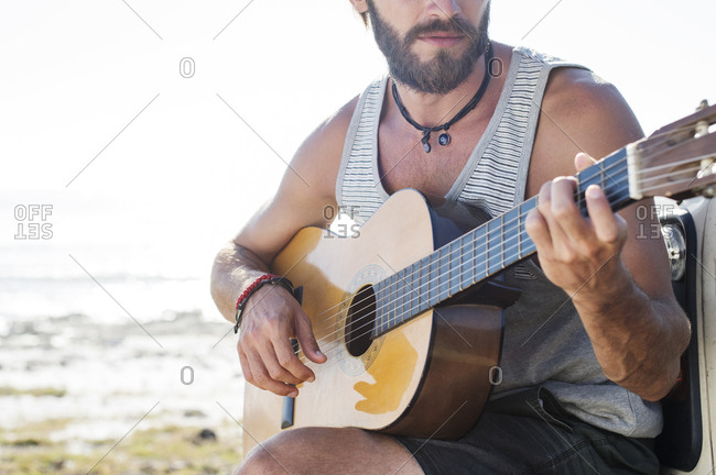 Midsection of man playing guitar while sitting on off-road vehicle during sunny day