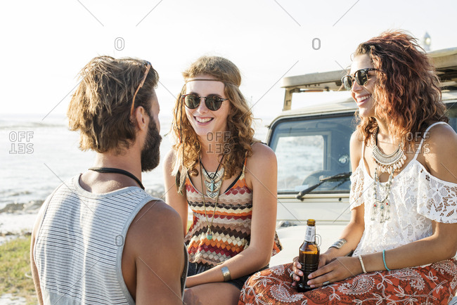 Man talking to female friends enjoying beer while sitting on off-road vehicle