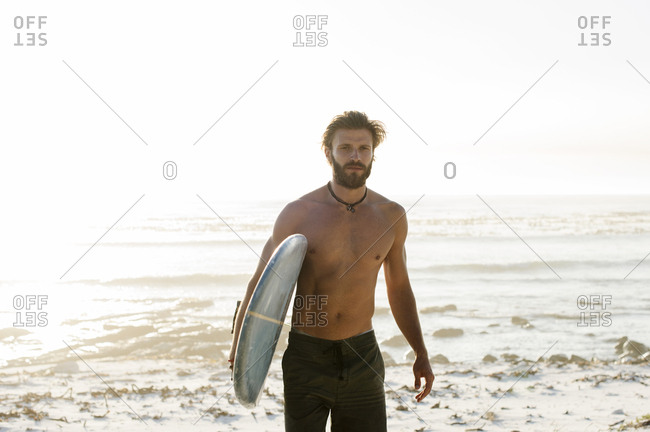 Portrait of shirtless man carrying surfboard while walking at beach against clear sky