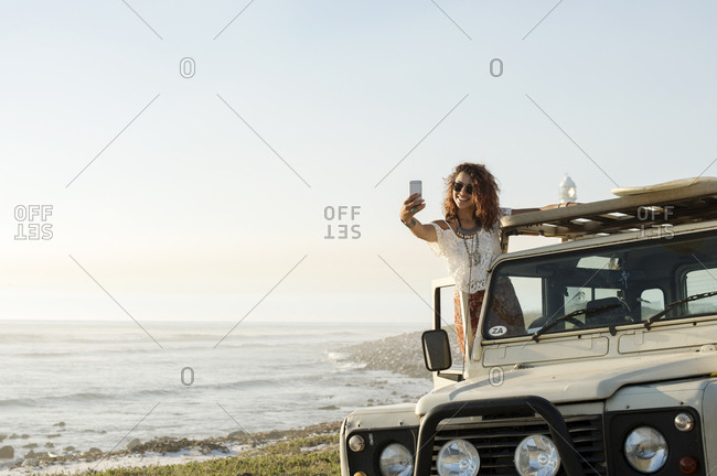 Happy woman taking selfie while standing on off-road vehicle at beach
