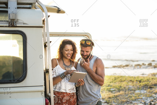 Woman showing tablet computer to boyfriend while standing by off-road vehicle at beach