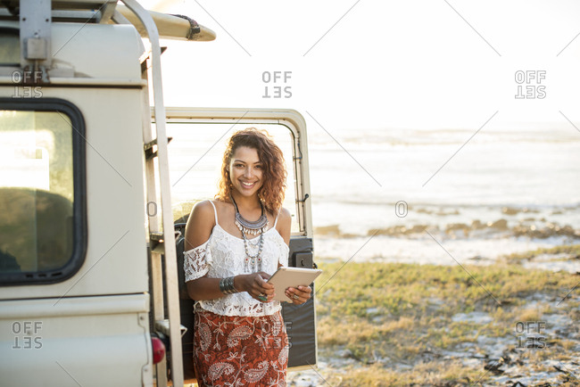 Portrait of happy woman with tablet computer standing by off-road vehicle at beach