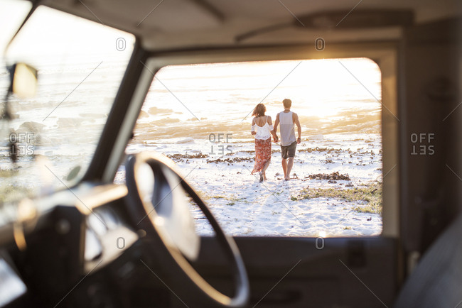 Rear view of couple walking at beach seen through off-road vehicle window