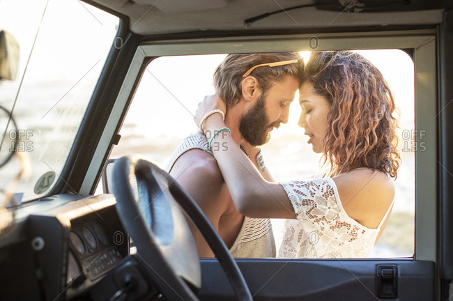 Couple romancing while standing by off-road vehicle seen through window