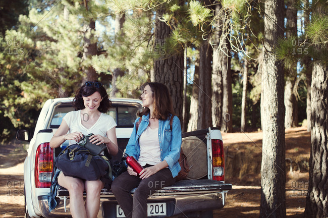 Happy female friends talking while sitting on pick-up truck in forest