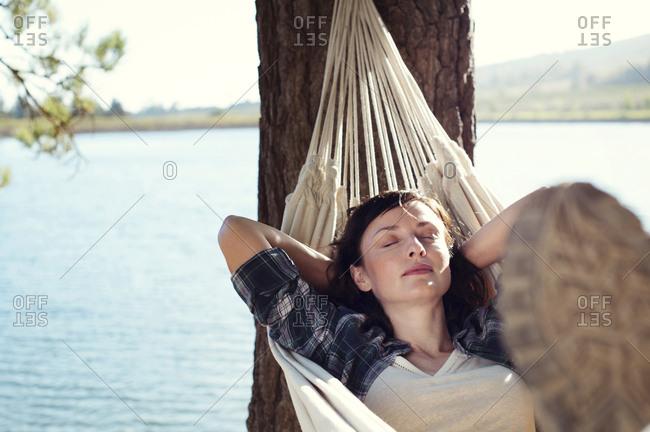Woman sleeping on hammock at lakeshore