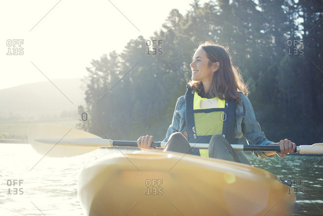 Smiling woman kayaking on lake against sky during sunny day