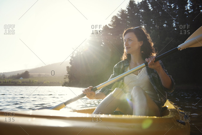 Smiling woman looking away while kayaking on lake during sunny day