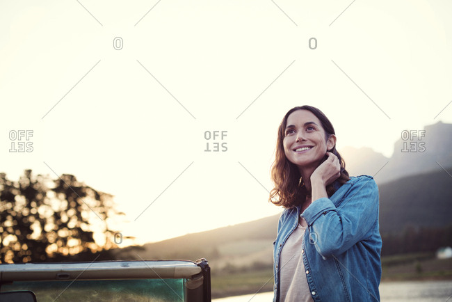 Woman looking away while standing by convertible car against clear sky during sunset