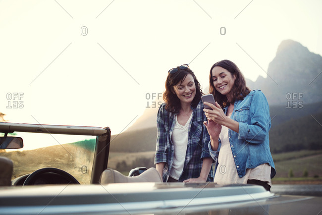Smiling woman showing mobile phone to friend by convertible car during sunset