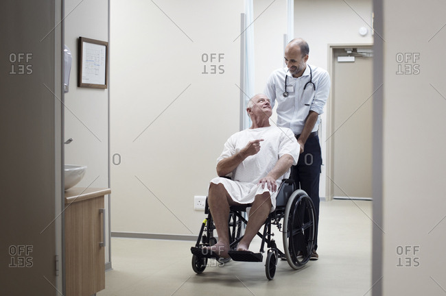 Doctor carrying patient on wheelchair in corridor